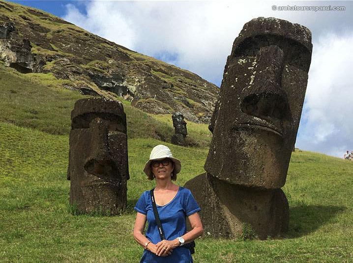 Touriste devant deux têtes de Moai à l'Ile de Pâques